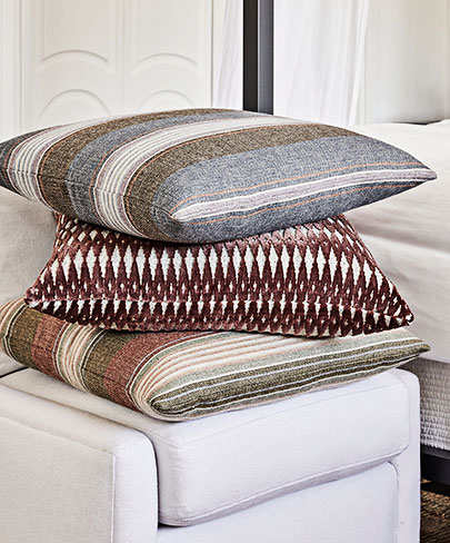 Three pillows stacked on an ottoman